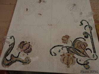 Mosaïque de Sabine représentant un motif floral art déco en marbre, galets et pierres fines.