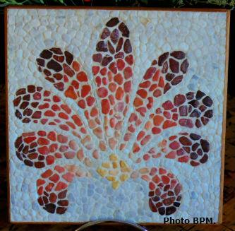 Photo mosaïque de Sara, représentant une palmette en galets.