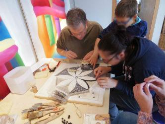 Public du musée Fenaille participant à la réalisation de la mosaïque collective lors des Journées Nationales de l