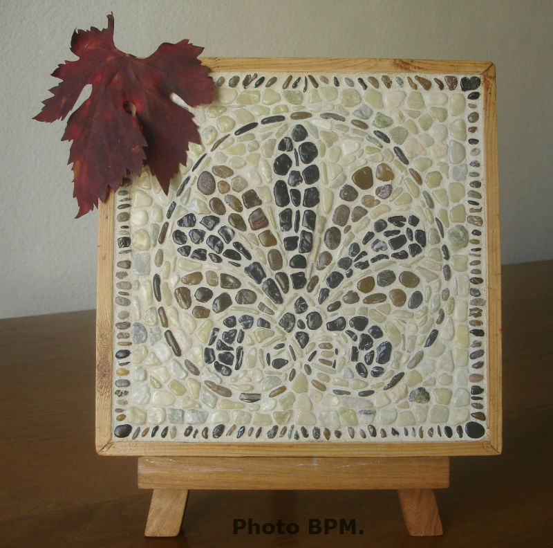 Ceci est une mosaïque en galets représentant une palmette de format 25 x 25 cm.
