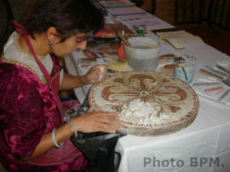 Ceci est une photo de Béatrice Pradillon-Marques en train de réaliser une mosaïque en marbre.
