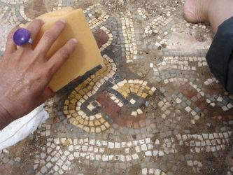 Ceci est une photo de Béatrice Pradillon-Marques en train de nettoyer une mosaïque à Rabaçal en 2014.