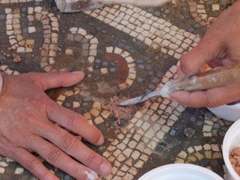 Ceci est une photo de détail de Béatrice Pradillon-Marques en train de restaurer des mosaïques à la villa romaine de Rabaçal.