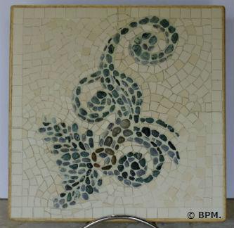 Ceci est une photo de la mosaique de Chantal, en galets et grès cérame représentant un motif végétal à volutes.
