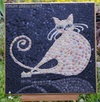 Ceci est une photo de la mosaique de Chantal, en galets et fond en marbre, représentant un chat.