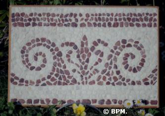 Ceci est une photo de la mosaique de Jean-François, réalisé en galets représentant un motif végétal.