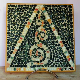 Ceci est une photo de la mosaique de Régine en galets, représentant un motif géométrique.