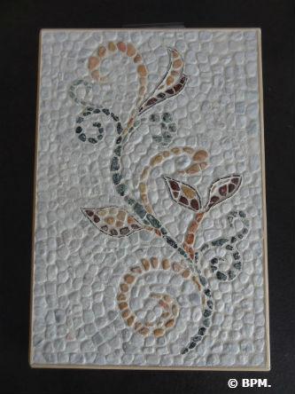 Ceci est une photo de la mosaïque de Sandrine, en galets, représentant un motif floral.