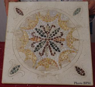Mosaiquede M-Paule représentant un motif floral tout en galets.