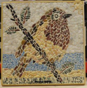 Mosaique de Jean, tout en galets, représentant un oiseau sur une branche.